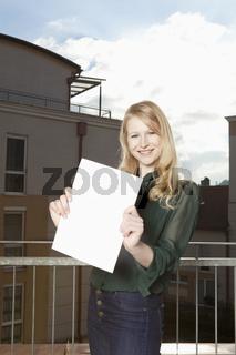 Junge Frau am Balkon zeigt Blatt mit Textfreiraum