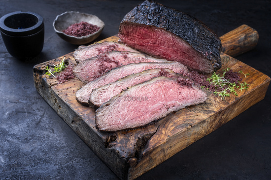 Traditional Commonwealth Sunday roast with sliced cold cuts roast beef with herbs and salt served as close-up on an old rustic wooden board