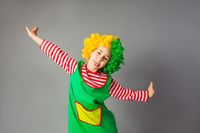 The funny little girl in a clown uniform