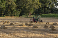 Old tractor in a field with straw bales