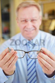 Optiker zeigt Brille bei Beratung
