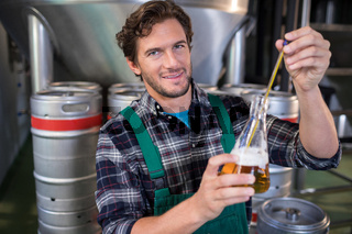 Portrait of smiling worker examining beer at factory
