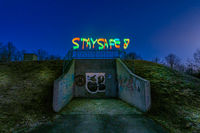 Best wishes in times of Corona and the Covid-19 virus, lightpaining at night with STAY SAFE painted colorful at the top of a bunker.