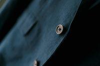 Close-up of a brown button on a navy blue men's blazer.