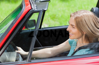 Smiling woman driving red cabriolet