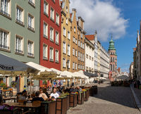 people enjoy drinks and food in one of the many street cafes and restaurants in the hsitoric old town of Danzing on a beautiful summer day