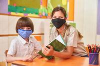Erzieherin hilft Kind mit Maske in der Schule