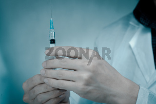 doctor with medical syringe in hand