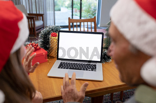 Caucasian woman and senior man having video call on laptop with copy space at christmas time