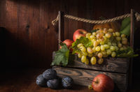 grapes and other fruits on a dark wooden background in a rustic style