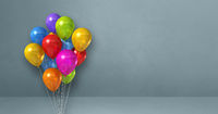 Colorful balloons bunch on a grey wall background. Horizontal banner.