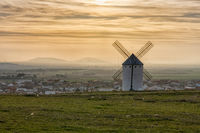 whiteashed Spanish windmill above the plains of La Mancha in central Spain at sunset