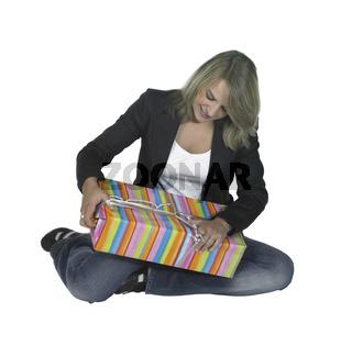 sitting girl unpacking a present