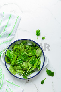 Organic raw spinach in bowl on white background