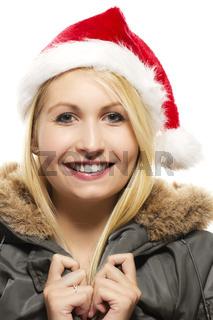 lachende schöne blonde frau in einem parka trägt eine nikolausmütze