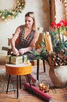 Happy blonde woman sitting on chair in new year festively packing christmas gift box