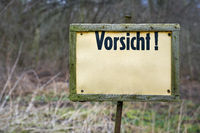 Sign on a forest path with the inscription Caution (Vorsicht) with space for more text