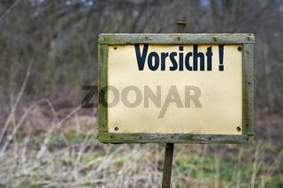 Schild an einem Waldweg mit der Aufschrift Vorsicht