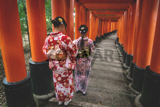 Women in kimono in tunnel of orange torii gates at Fishimi Inari Taisha shrine in Kyoto, Japan