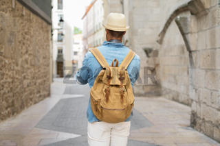 Rear view of a young man with backpack walking on the street in the old town.