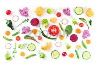 Many fresh vegetable slices, overhead flat lay shot on a white background