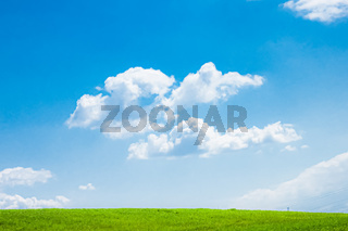 Green field and blue sky with clouds, beautiful meadow as nature and environmental background
