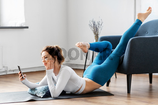 woman with smartphone stretching yoga at home