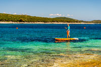 Young girl sup board with a paddle in hand - front view - the calm surface of the turquoise sea - copy space