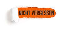 Hole in white paper with torns edges - Important in german - Nicht vergessen
