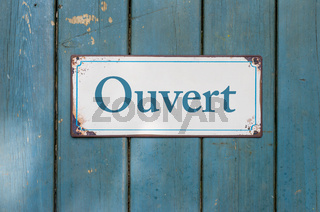 Old sign with the inscription Open in french - Ouvert