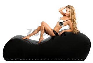 Seductive young woman with magnificent hair in lingerie posing on a tantra chair