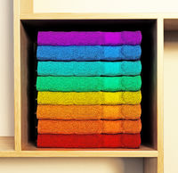 Stack of multi-colored towels standing on the shelf. 3D illustration