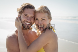 Portrait of smiling couple embracing at beach