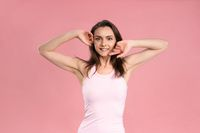 Charming young woman holding hands up with no makeup, skin care concept, attractive brunette girl in pink t-shirt on pink background. Human emotions, facial expression concept. Beauty concept