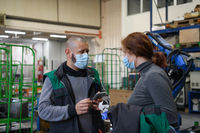 Industrial workers with face masks protected against corona virus discussing about production in factory. People working during COVID-19 pandemic.