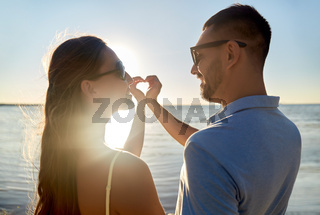 happy couple showing hand heart on summer beach