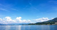 Idyllic Swiss landscape, view of lake Zurich in Richterswil, Switzerland, mountains, blue water of Zurichsee, sky as summer nature and travel destination, ideal as scenic art print