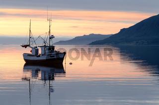 Fischerboot bei Sonnenuntergang im Fjord