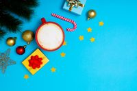 Composition of christmas decorations with baubles, presents, mug and copy space on blue background