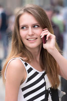 portrait of cute girl is talking via mobile phone on the street and smiling