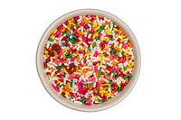 Rainbow sprinkles in white ceramic bowl on white background.
