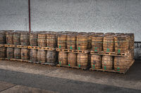 Rows of large wooden barrels on pallets with whiskey or wine ready for transportation