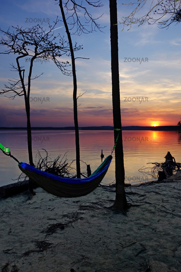 A hammock hanging in the trees at sunset on the shore of Jordan Lake State Park campground in North Carolina