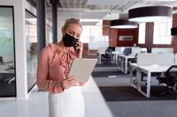 Caucasian businesswoman wearing face mask standing in office using tablet and talking on smartphone