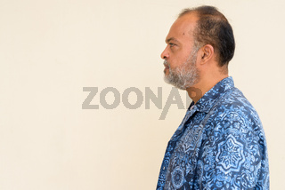 Profile view of handsome bearded Indian man against plain wall