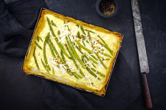 Traditional French Tarte with green asparagus served as top view in backing form