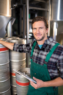 Smiling worker holding clipboard while standing by kegs at warehouse