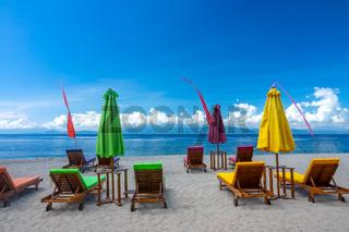 Empty Sun Loungers and Umbrellas on a Tropical Beach