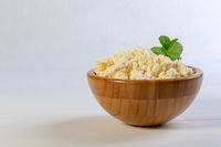 Homemade cottage cheese in a wooden bowl.
