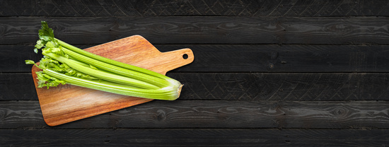 Celery branch bunch on a cutting board. Isolated on black wood banner background